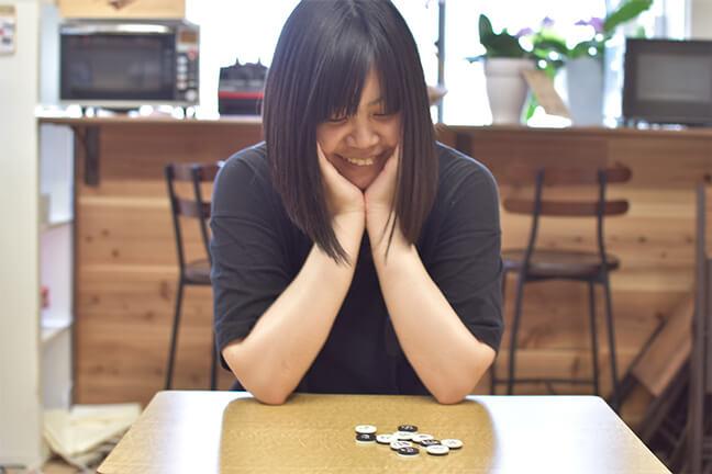 可愛くデザインされたオセロを見て微笑むデザイナーのともぞう