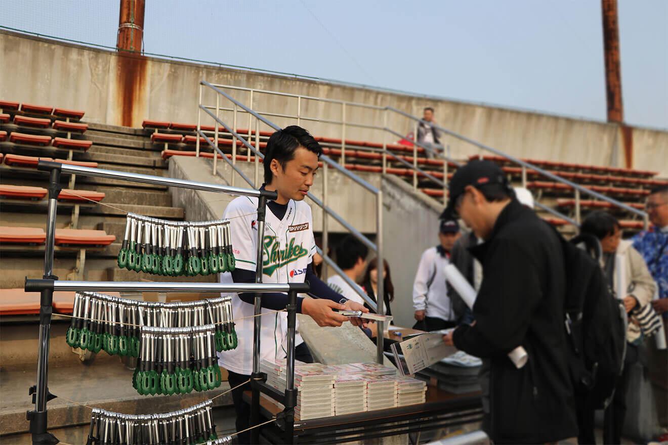 球場でバトルスタディーズ を配る松本オーナー